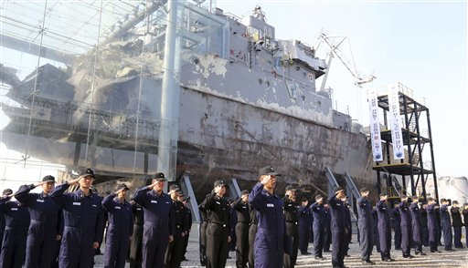 """South Korean navy sailors pay tribune to mark the third anniversary of the sinking of South Korean naval ship """"Cheonan"""" in front of the wreckage of the vessel at the Second Fleet Command of Navy in Pyeongtaek, south of Seoul, on Tuesday."""