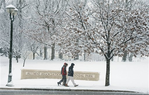 James Madison University students walk across a snow-covered campus in Harrisonburg, Va., Sunday evening. A meteorologist with the National Weather Service in Sterling, Va., said more than 3 inches of snow had been reported by 8 a.m. Monday at Washington Dulles International Airport, and more than an inch at Reagan National Airport.