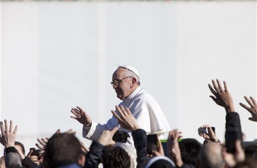 Pope Francis waves to crowds as he arrives to his inauguration Mass in St. Peter's Square at the Vatican on Tuesday. Pope Francis urged world leaders and ordinary people to protect the environment, the weakest and the poorest.