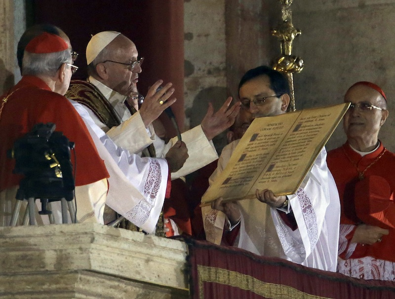 Pope Francis speaks from the central balcony of St. Peter's Basilica at the Vatican, Wednesday, March 13, 2013. Cardinal Jorge Bergoglio who chose the name of Francis, is the 266th pontiff of the Roman Catholic Church. (AP Photo/Luca Bruno)