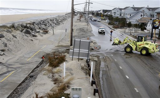 Crews clear a flooded road Thursday in Sea Bright, N.J., after an overnight storm caused the ocean to breach a temporary dune. The lingering late-winter storm brought new damage Thursday to parts of the Jersey shore still struggling to recover from Superstorm Sandy.