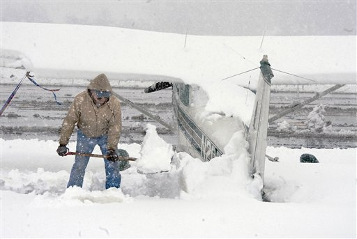 Pilot John Harsh shovels snow off of the tail of his Cessna 172 airplane at the Shenandoah Valley Regional Airport during heavy snow Wednesday in Weyers Cave, Va. Some areas of the Central Shenandoah Valley received over a foot of snow from the storm.