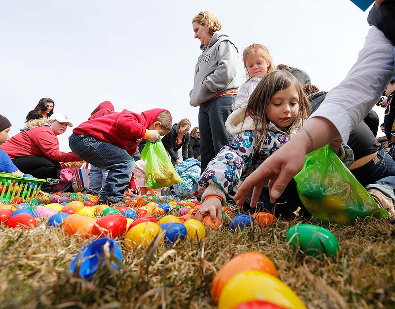 Next Level Church hosts an Easter egg drop at Payson Park in Portland on Sunday. Courtney Lane-Hebert of Lisbon watches as her son, Mason Hebert, 3, collects eggs. At right, Morgan McLaskey, 6, of Westbrook fills her bag.