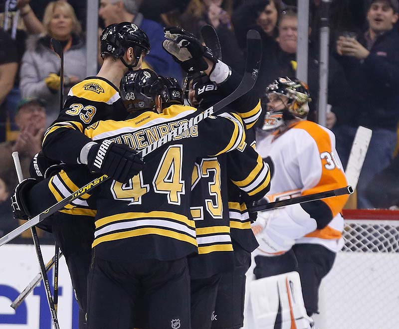 Chris Kelly, 23, celebrates his goal with teammates Zdeno Chara, 33, and Dennis Seidenberg as Flyers goalie Ilya Bryzgalov stands in the goal in the first period Saturday in Boston. The Bruins won 3-0.