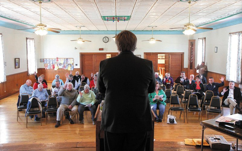 Residents vote on an article as moderator David Benier presides over the annual Benton Town Meeting, inside the Benton Grange Hall, on Saturday.
