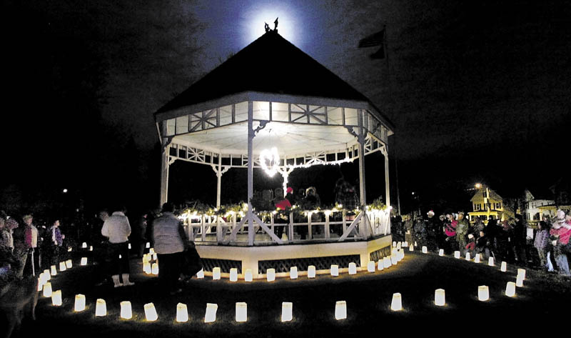 This 2006 file photo shows the moon rising behind people standing around the gazebo on Gardiner Common at the conclusion of the hospice luminaria lighting event on the Common in Gardiner. The structure, torn down in 2012, will be replaced, but when and what it will look like are open questions.