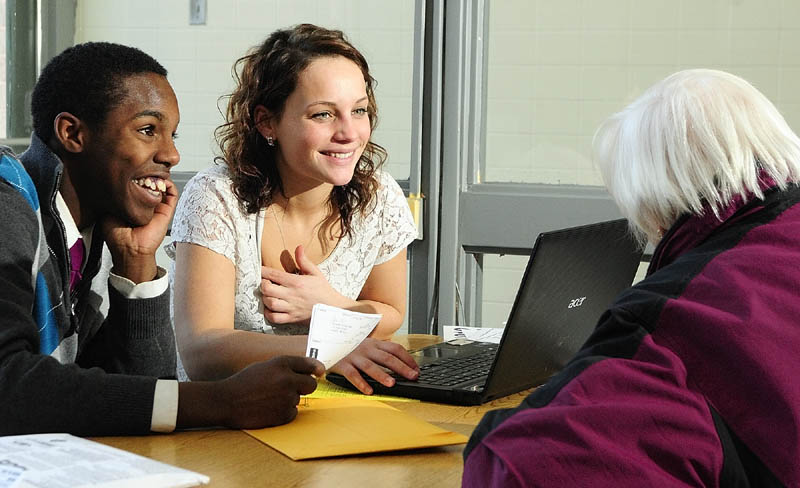 Capital Area Technical Center students Dayshawn Roberts, left, and Emma Madison chat with tax preparation client Eula Roberts, of Augusta, as they do her taxes on Thursday at their school in Augusta.