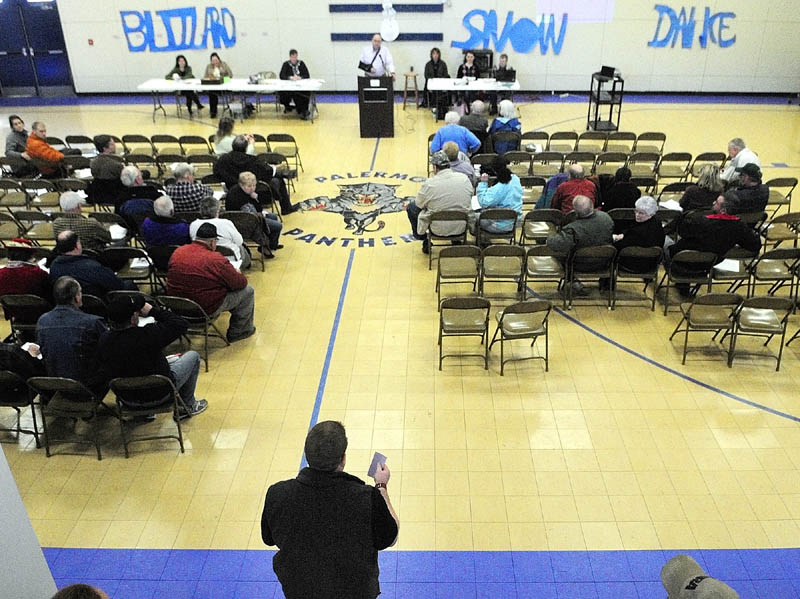 Ryan Harmon, standing lower center, speaks during a debate on road paving during the annual town meeting on Saturday at the Palermo Consolidated School.