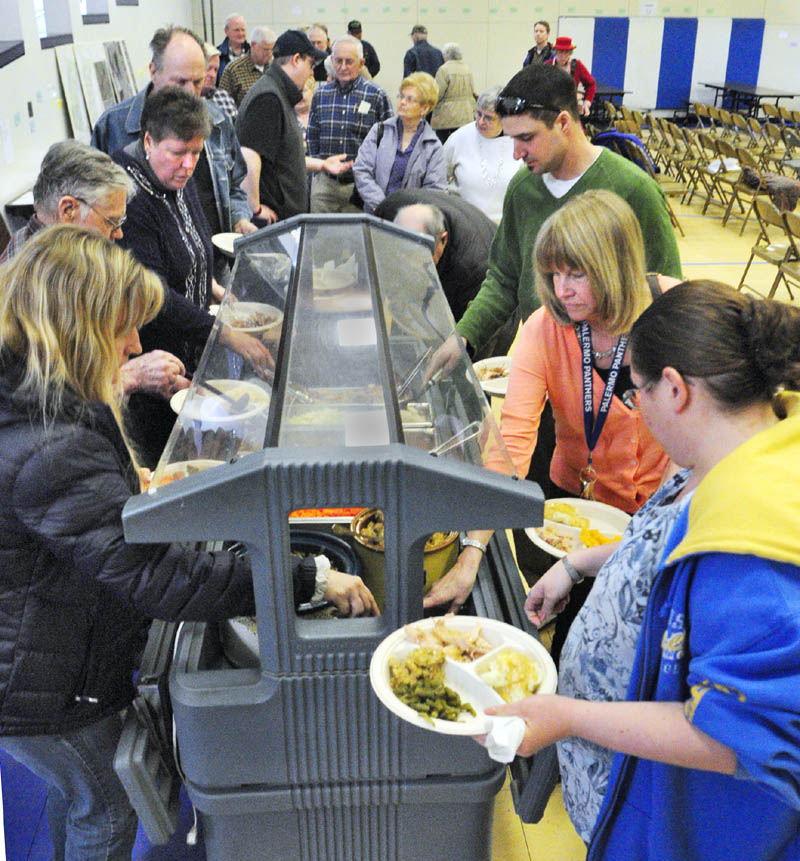 People serve themselves a turkey dinner during a lunch break in the annual town meeting on Saturday at the Palermo Consolidated School. The lunch was prepared by members of the Branch Mills Grange.