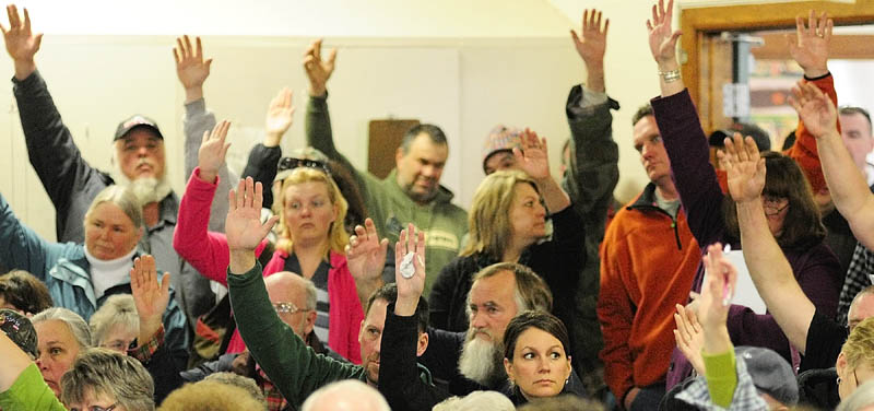Residents raise their hands to vote during the Pittston town meeting on Saturday in the Pittston Elementary School gym.
