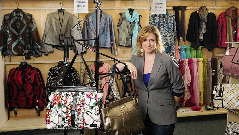 Stacy Gervais, owner of Stacy's Hallmark, stands next to a display of clothing and bags in her Water Street store on Thursday in downtown Augusta. She said that she plans to do some renovations and increase the clothing area of her shop while keeping the cards and other products.