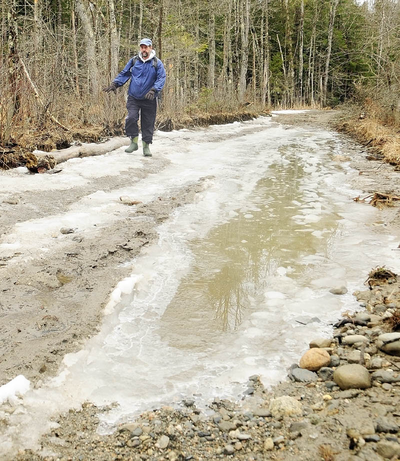Bill Seekins walks along a flooded section of access road on Thursday during a tour of Thurston Park in China. Seekins said he applied to have the Maine National Guard engineering battalion work on the road as part of their training over this summer.