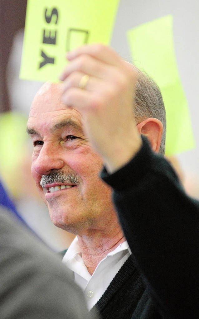 Earle McCormick holds up his voting card during the West Gardiner Town Meeting on Saturday in the town's fire house. Before the meeting, he was announced as unofficial winner of the race for selectman, pending a recount.