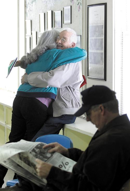 Rome resident Richard H. LaBelle smiles while getting a hug from friend Alice VanDerwerken, before the start of the annual Rome town meeting on Saturday. VanDerwerken said she and LaBelle have known each other for more than 20 years.