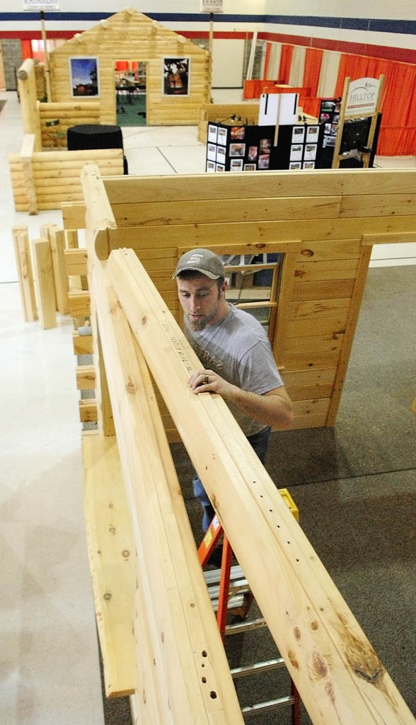 Matt Rutchick puts the top layer on a display model that he and other workers from Coventry Log Homes, based in Woodsville, NH, put together on Thursday inside the Augusta Armory. The 11th Annual Maine Log Home, Timber Frame, & Restoration Show will be held there this weekend. Show hours are Friday noon to 7p.m., Saturday, 10 a.m. to 7 p.m., and Sunday 10 a.m. to 4 p.m.