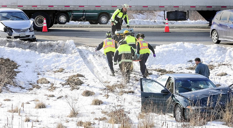 Augusta firefighters carry a person on backboard away from a car that slid off the road around toward a waiting stretcher around 5 p.m. on Friday, after a three-vehicle collision near Riverside Drive and Route 3 in Augusta. The accident took place in the northbound lane of Riverside Drive, just before the traffic light at Route 3. Additional details were unavailable early Friday evening.