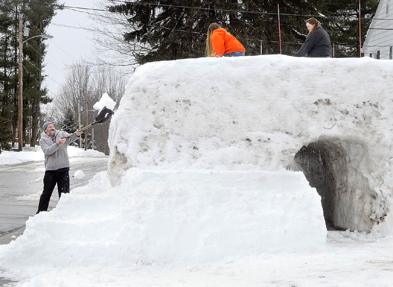Steven St. Pierre tosses shovelful of snow on Wednesday up onto a snow fort he and his daughters Shania St. Pierre, center, and Natasha St. Pierre, built on Sixth Avenue in Augusta.
