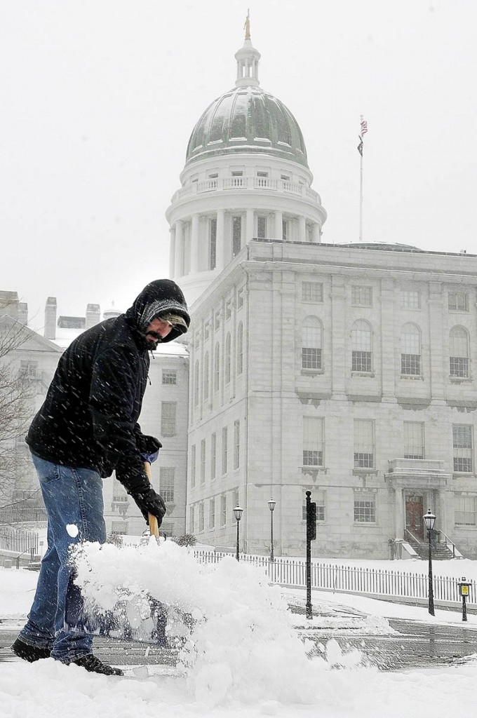 Jason Sirios shovels snow at the State House complex on Tuesday in Augusta. He was part of the Bureau of General Services crew clearing sidewalks and lots.