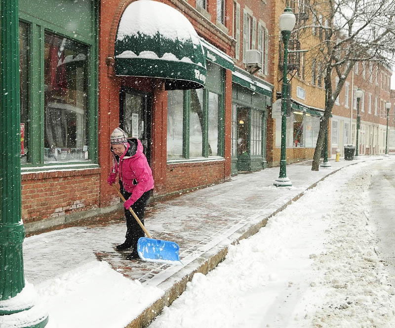 April Hall shovels snow from a late winter storm in front of the Reny's store, where she works, on Tuesday in Gardiner.