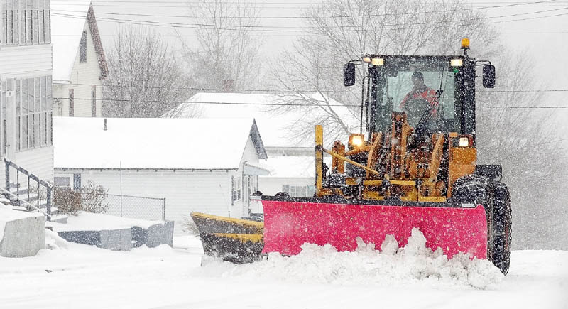 A city front-end loader pushes snow from Monroe Street as more falls during a late winter storm on Tuesday in Augusta's Sand Hill neighborhood.