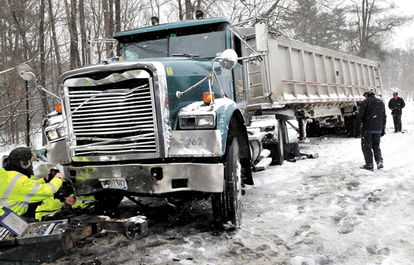 Tow truck workers prepare to haul a front-end damaged construction truck following a collision with a vehicle on snow-covered Route 139 in Benton on Tuesday.