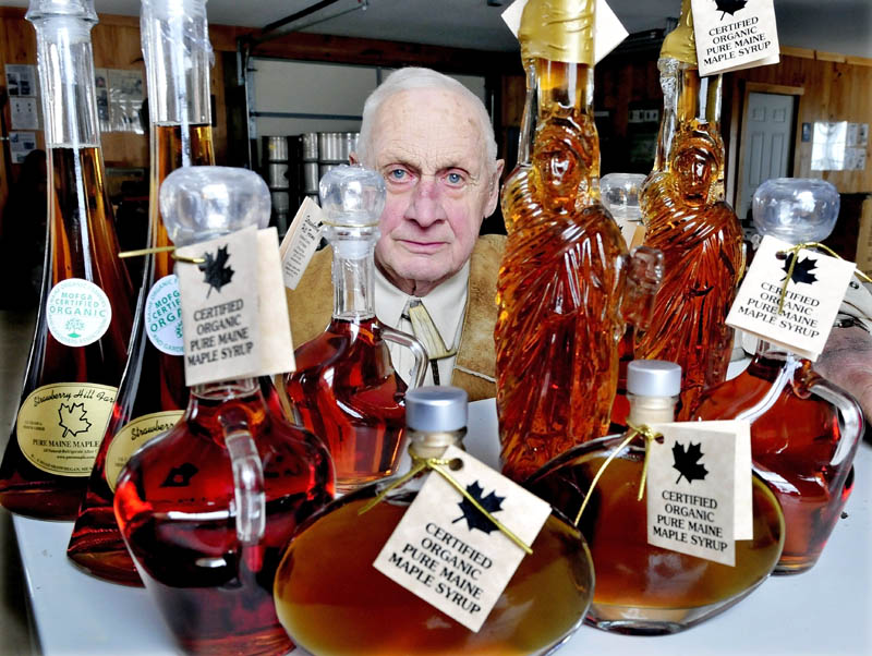 Jack Steeves with some of the various glass containers filled with maple syrup made at Strawberry Hill Farms in Skowhegan.