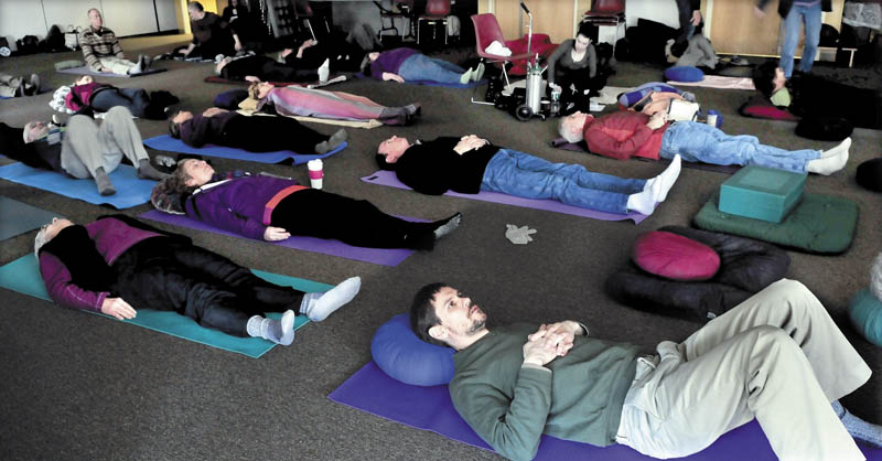Western Maine Buddhism seminar presenter Jeb Enoch, foregrond, and participants prepare for meditation during the event on Sunday at the University of Maine in Farmington.
