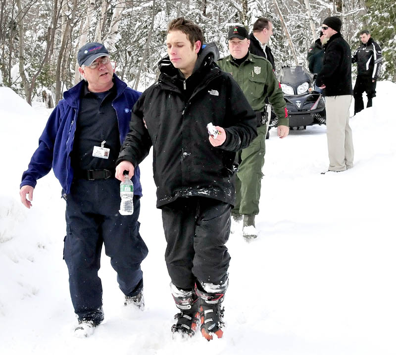 Missing skier Nicholas Joy is escorted to an ambulance by Peter Boucher of Northstar Ambulance when he emerged from the woods last Tuesday. Snowmobiler Joseph Paul, far right, found him walking on a trail near Sugarloaf Mountain.
