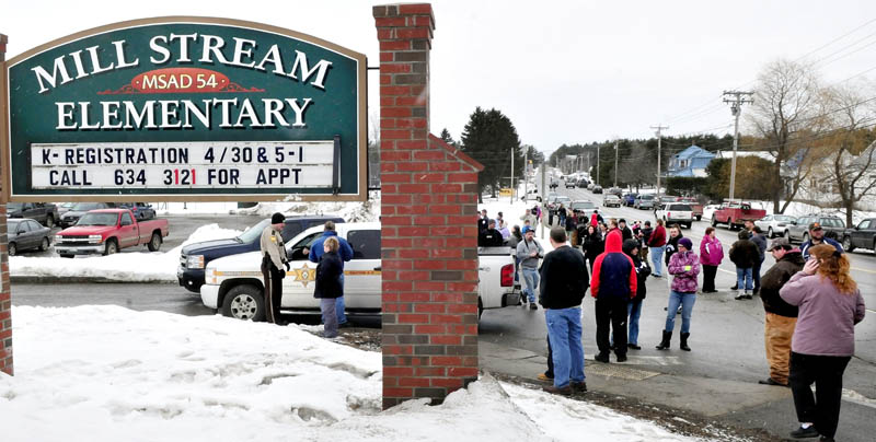 "Ruth Perkins speaks with police as parents assemble outside the entrance of the Mill Stream Elementary School in Norridgewock following a report of a man with a rifle nearby on Monday. Police searched the area but did not locate a suspect. Referring to her grandchildren, Perkins said,"" I just want to get them in my arms."""