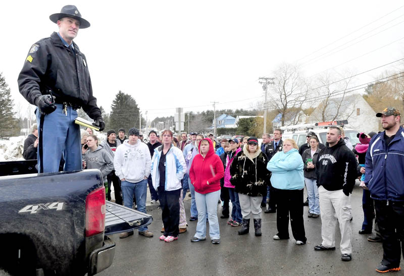 Sgt. Aaron Hayden of the Maine State Police updates parents outside the Mill Stream Elementary School in Norridgewock, regarding the status of a search for a report of a man with a rifle near the school, on Monday. Hayden told the parents that no one was found and they could join their children following the school lockdown.