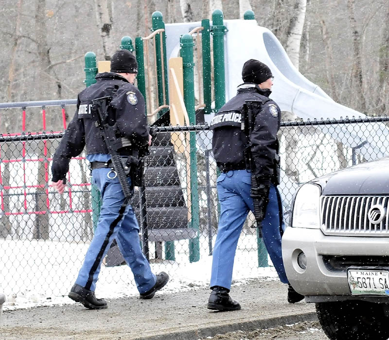Maine State Police troopers walk past a playground during a lockdown at the Mill Stream Elementary School in Norridgewock, while searching for a reported man with a rifle, on Monday.