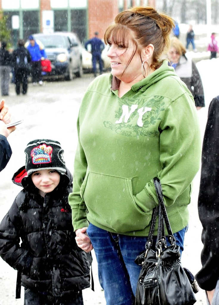 Parent Kerry Falvey holds on to her son, Jaden, after police allowed parents to reunite with their children following a lockdown of the Mill Stream Elementary School in Norridgewock on Monday. Police searched the school grounds after a report of a man nearby with a rifle.