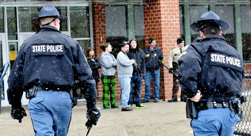 Maine State Police approach parents waiting to enter the Mill Stream Elementary School in Norridgewock following a lockdown on Monday. Police searched the school grounds for a man with a rifle but no suspect was located.