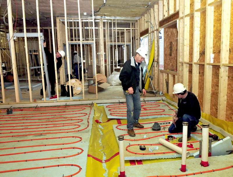 Wright-Ryan company Superintendent Millard Nadeau, standing, speaks with Dave Poulin, as he installs radiant heat material in the floor of a prisoner cell inside the new Waterville police building on Tuesday. Nadeau said the project is on schedule and slated to be finished this June.