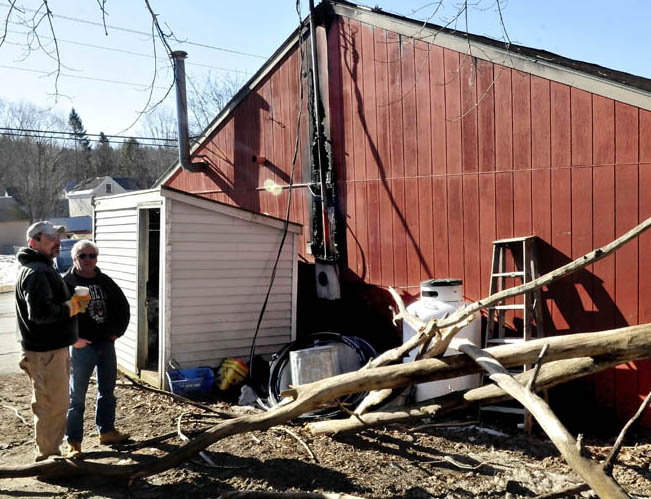 Scott Bouchard, left, speaks with a customer outside his business, Oakland Redemption and Discount Beverage, on Monday. The fallen tree limb, foreground, struck a power line into the building Sunday evening, causing fire that caused extensive damage to the building.