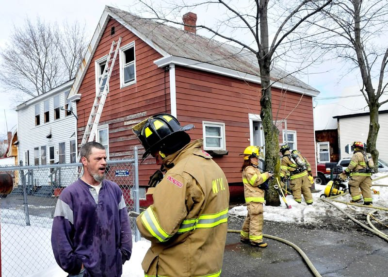 Homeowner Barry Dolley speaks with Waterville firefighter Lt. John Gromek as other firefighters extinquish fire in the attic portion of Dolley's home on Sunday. Dolley said he was working in the home earlier and said sparks from a grinder may have ignited cellulose insulation. No injuries were reported and damage was contained to the attic, according to firefighters.