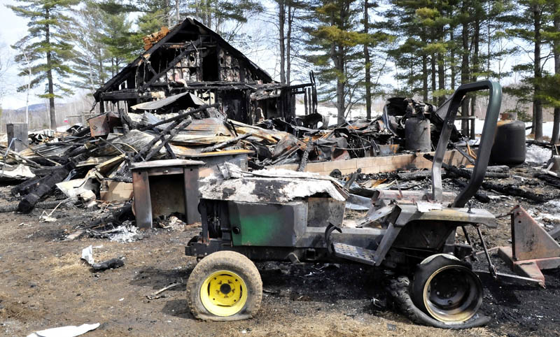 The remains of a home, garage and equipment at the property of Tellis Fenwick in Freeman Township, which were destroyed in a Saturday fire, as seen on Sunday, The home was located off the Freeman Ridge Road near the Kingfield and New Portland town lines.