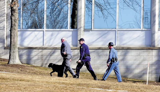 "Waterville Police Chief Joe Massey, left, who is also serving as interim chief in Fairfield, leads state troopers and a bomb-sniffing dog into Carter Hall on the Kennebec Valley Community College in Fairfield on Tuesday, after the word ""bomb"" was discovered in a ladies room earlier. The campus was evacuated as police searched the building."