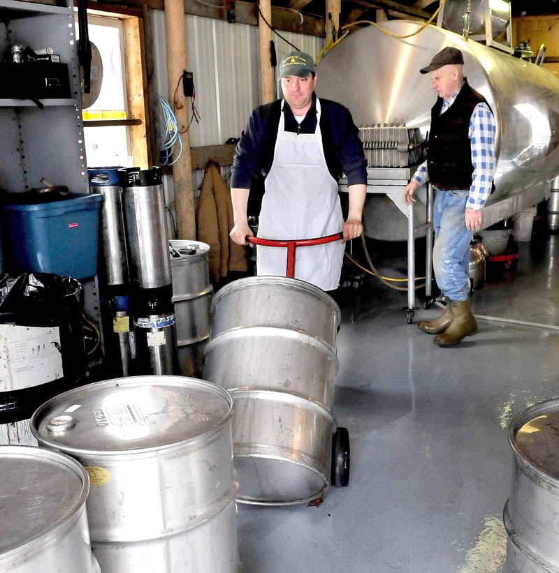 Jeremy Steeves moves a barrel filled with 40 gallons of hot maple syrup as his father, Jack, prepares to fill another barrel inside the sugar camp building at Strawberry Hill Farm in Skowhegan on March 11.