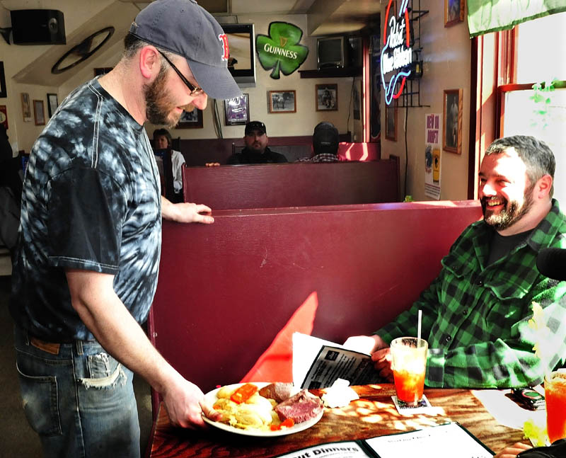 "Dugout Bar and Grill owner Shaun Riggs serves an Irish staple of corned beef and cabbage to George Poland at the Farmington eatery on Sunday. Riggs said he does not want to be a bar that sells liquor early in the morning, beginning a 6 a.m., that was allowed due to St. Patrick's day falling on a Sunday. ""It's an irresponsible thing,"" Riggs said."