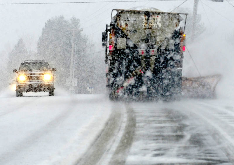 Tuesday's storm created slippery and sometimes whiteout driving conditions as a motorist passes a Maine Department of Transportation plow truck on U.S. Route 202 in Troy.