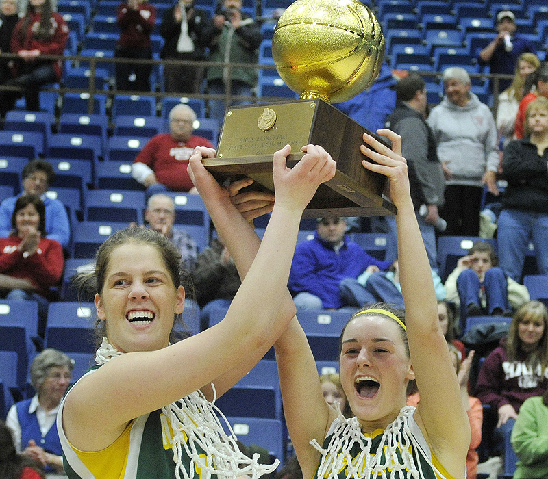 McAuley team captains Molly Mack and Allie Clement, right, hold up the state championship trophy after defeating Bangor 60-45 earlier this month.