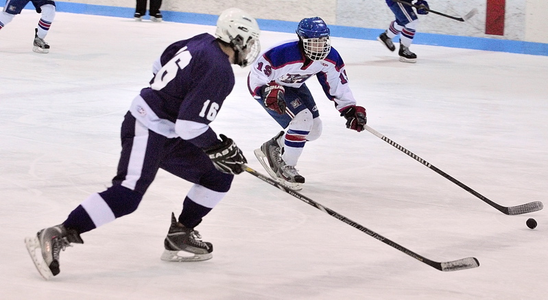 William Manning, left, of Hampden Academy chases Messalonskee's Jared Cunningham during their Eastern Class B boys' hockey semifinal Saturday at Sukee Arena. Messalonskee advanced with a 7-5 victory.