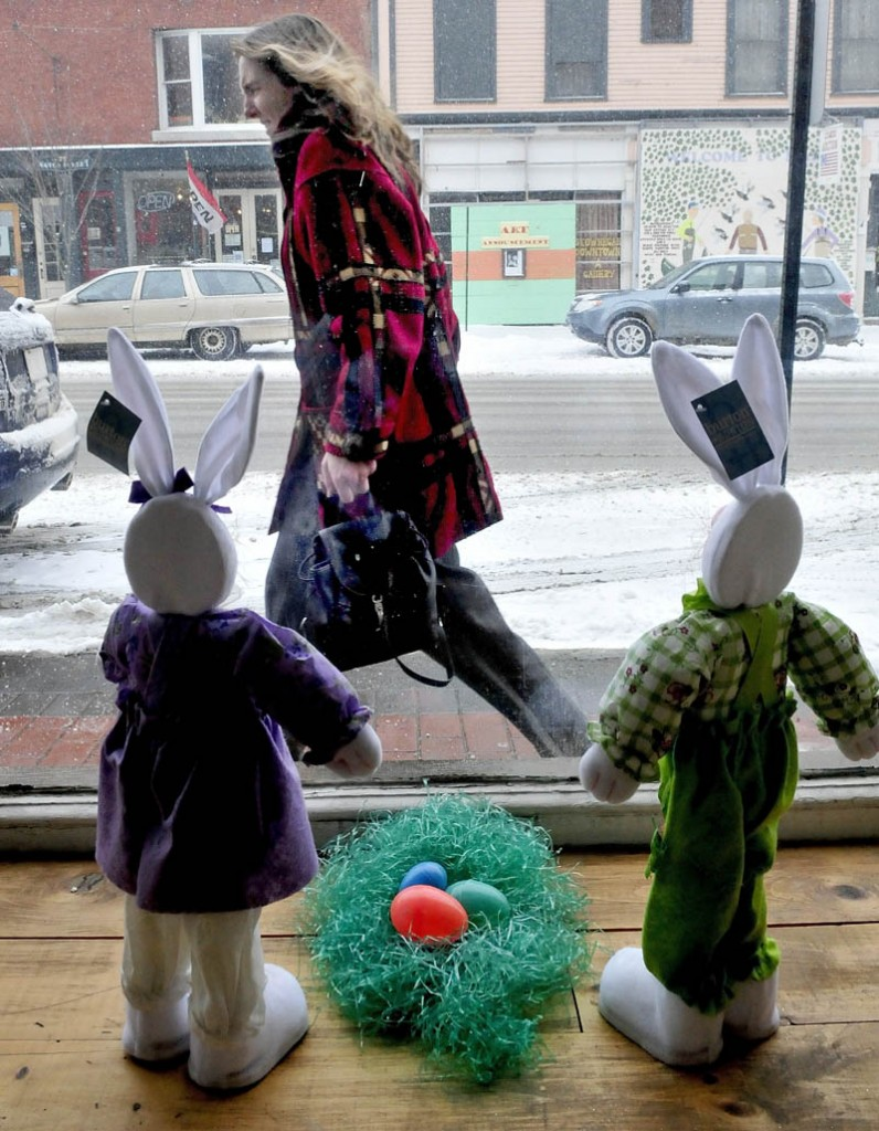 A late-winter snow storm greeted Maine on Tuesday and even these Easter bunnies were caught staring out the Variety Drug store window in Skowhegan, as Cynthia Cushing walks into the wind and snow blowing outside,