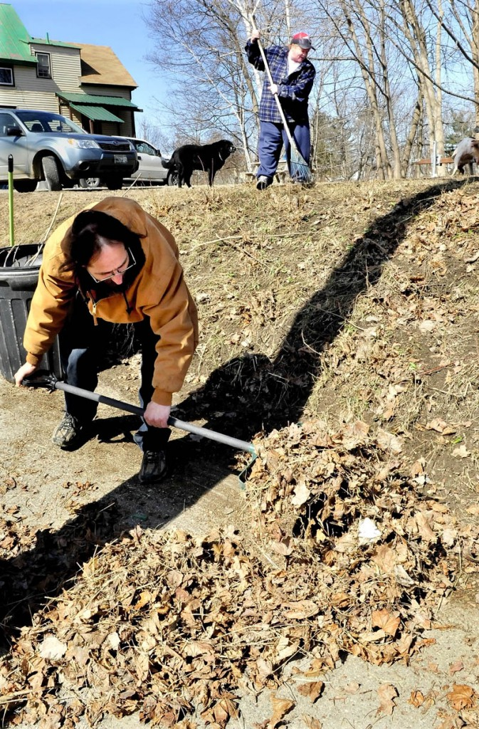 """Racing before the impending snowstorm forecast for Tuesday, Donald Grivois, front, and Kelly Danaher rakes old leaves and debris from a lawn on Sherwin Street in Waterville on Monday. """"We are just trying to clean up before the storm,"""" Danaher said."""