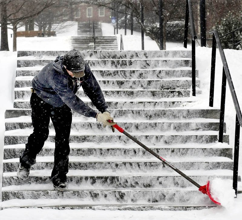 Colby College employee Nicholas Giroux finishes clearing snow from the seemingly endless set of stairs on campus in Waterville during the snow storm on Tuesday.