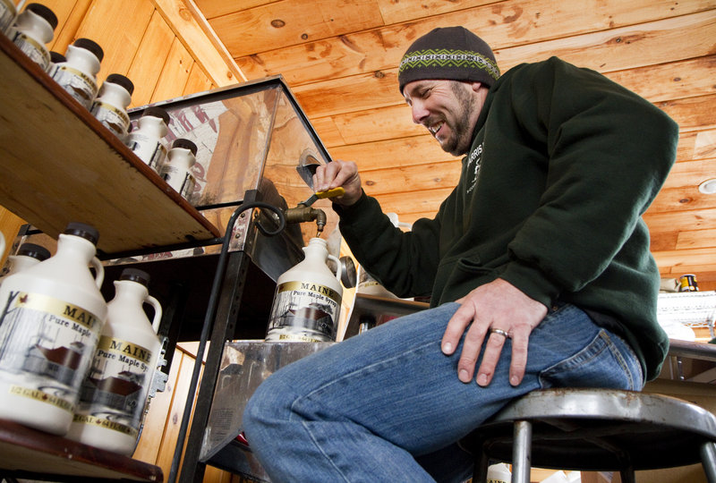 "Keith Harris of Harris Farm on Buzzell Road in Dayton fills jugs of maple syrup at the farm's sugarhouse last Thursday. ""What I want is what normal used to be,"" he said, speaking of this month's weather."