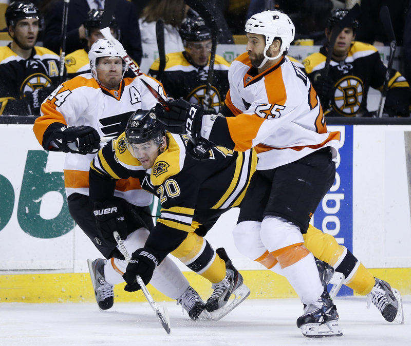Boston forward Daniel Paille avoids being sandwiched by Philadelphia's Kimmo Timonen, left, and Maxime Talbot during Saturday's game in Boston, won by the Bruins, 3-0.
