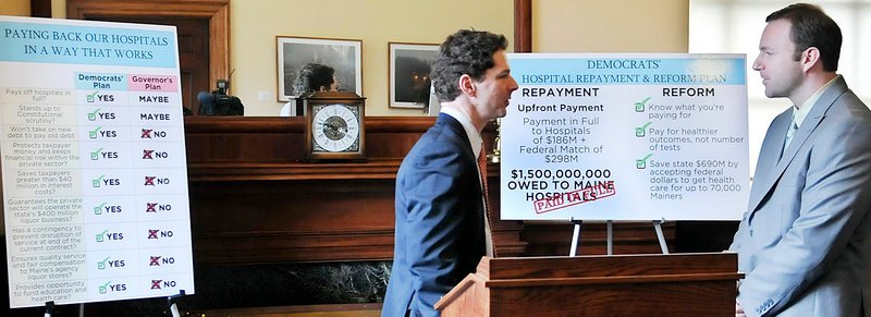 Senate President Justin Alfond, D-Portland, left, confers with Speaker of the House Mark Eves, D-North Berwick, after they unveiled a plan to repay state debt to hospitals by expanding the Medicaid program and receiving an upfront payment from the winning bidder of the state liquor contract.