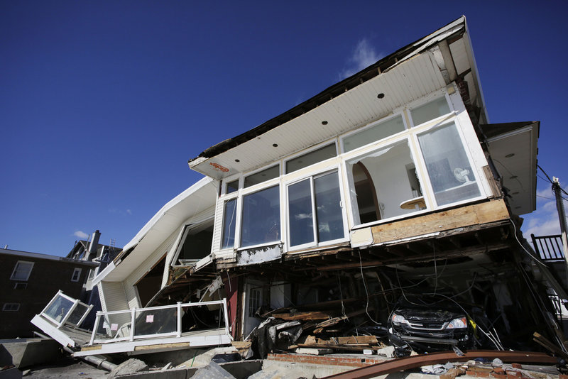 A car, lower right, is trapped in the wreckage of a beachfront house in the Far Rockaways in the Queens borough of New York in January, three months after Hurricane Sandy. States across the Northeast are creating plans to prepare for effects of climate change, but in Maine, Gov. Paul LePage's administration halted creation of a climate adaptation strategy.